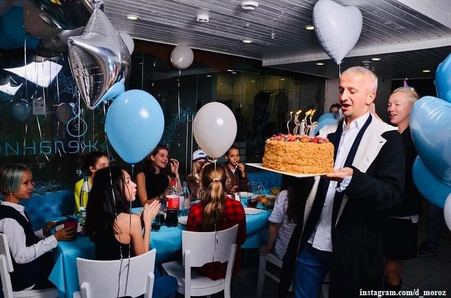 Константин Богомолов несет именинный торт дочери, а сзади стоит Дарья Мороз